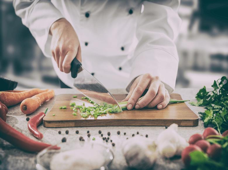 Restaurateurs qui découpe un légumes dans sa cuisine