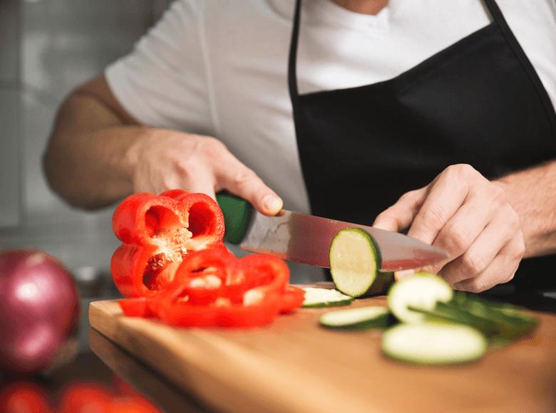 Restaurateurs qui découpe un poivrons dans sa cuisine